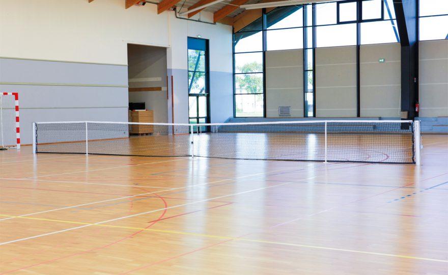 Poteau de tennis ovoide anodisé dans un gymnase