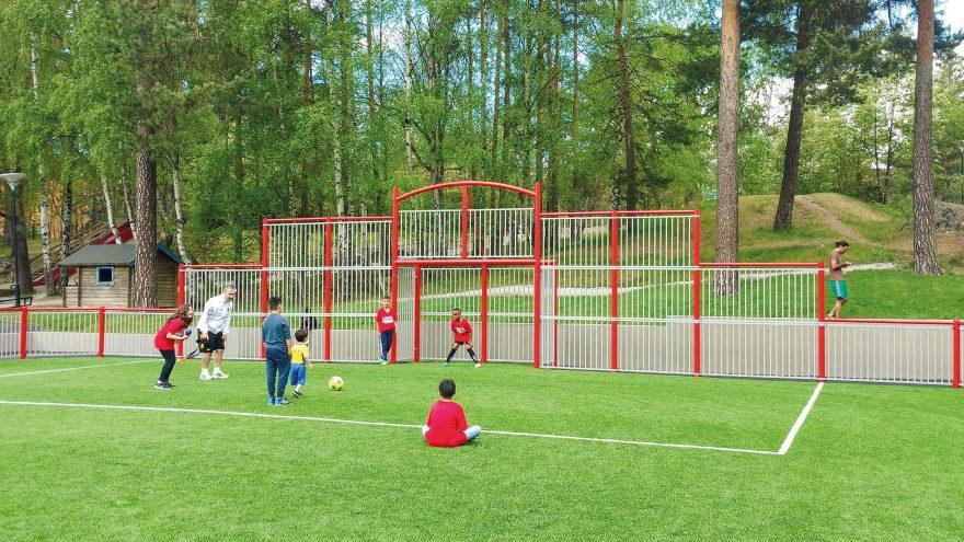 terrain multisport Metalu Plast Deauville rouge avec enfant qui jouent au football